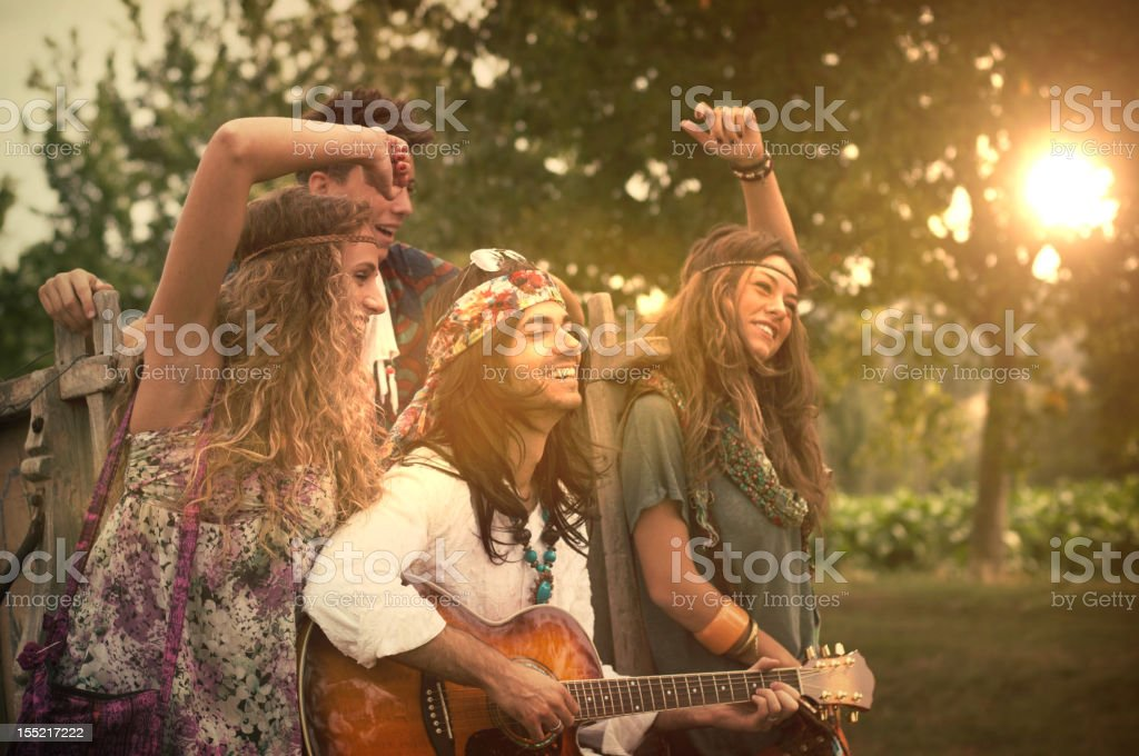 Hippies Dancing and Playing Guitar . 1970s style. stock photo