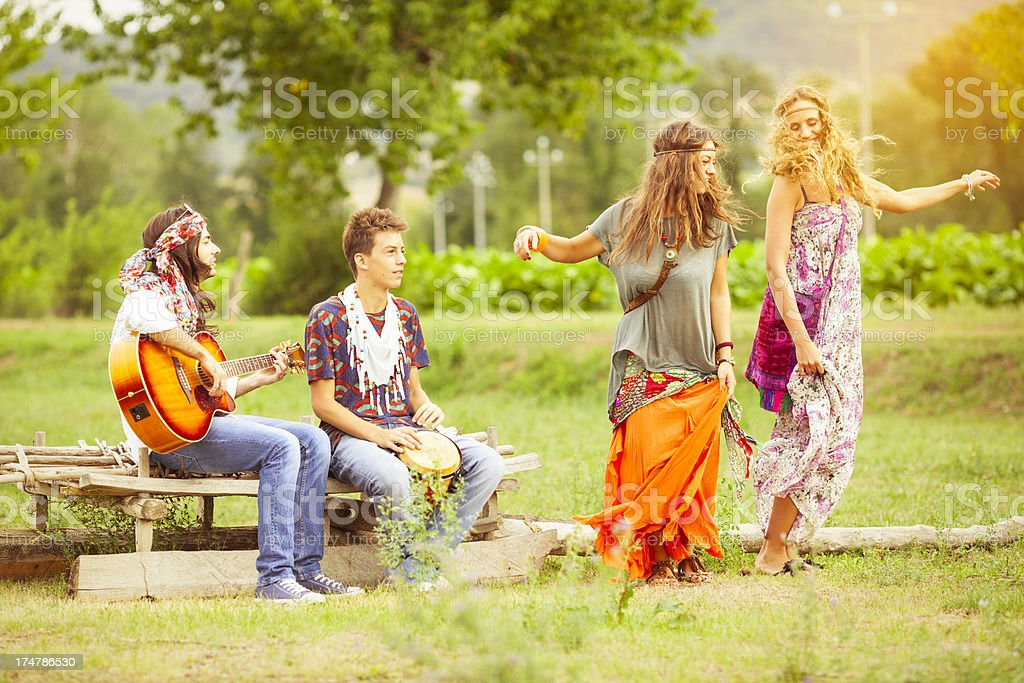 Hippies dancing and playing guitar stock photo
