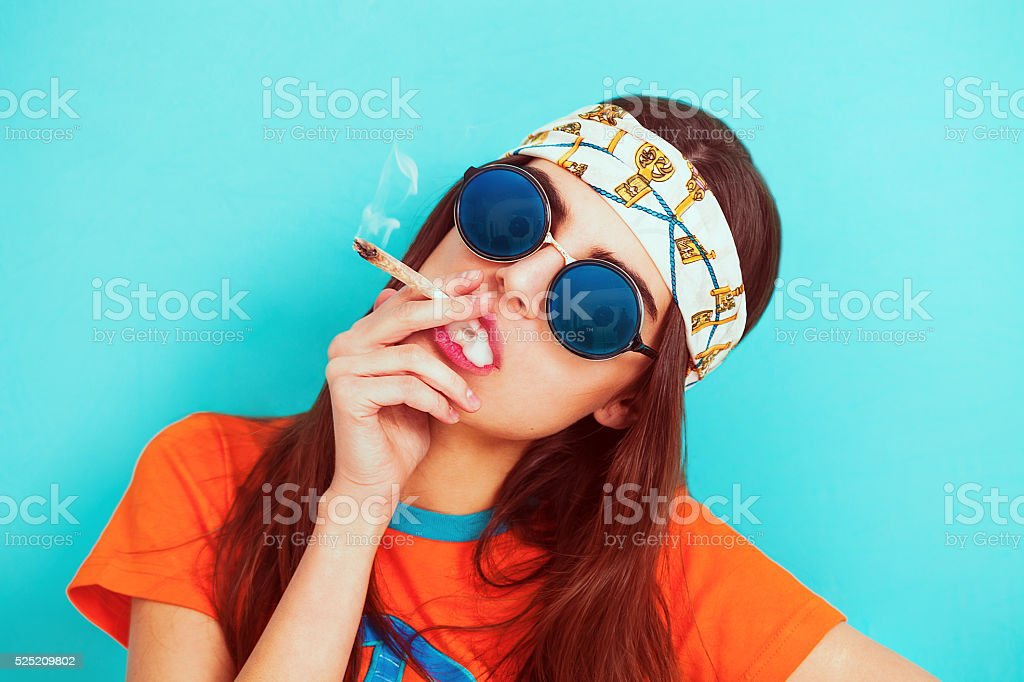 Hippy girl portrait smoking weed and wearing sunglasses stock photo