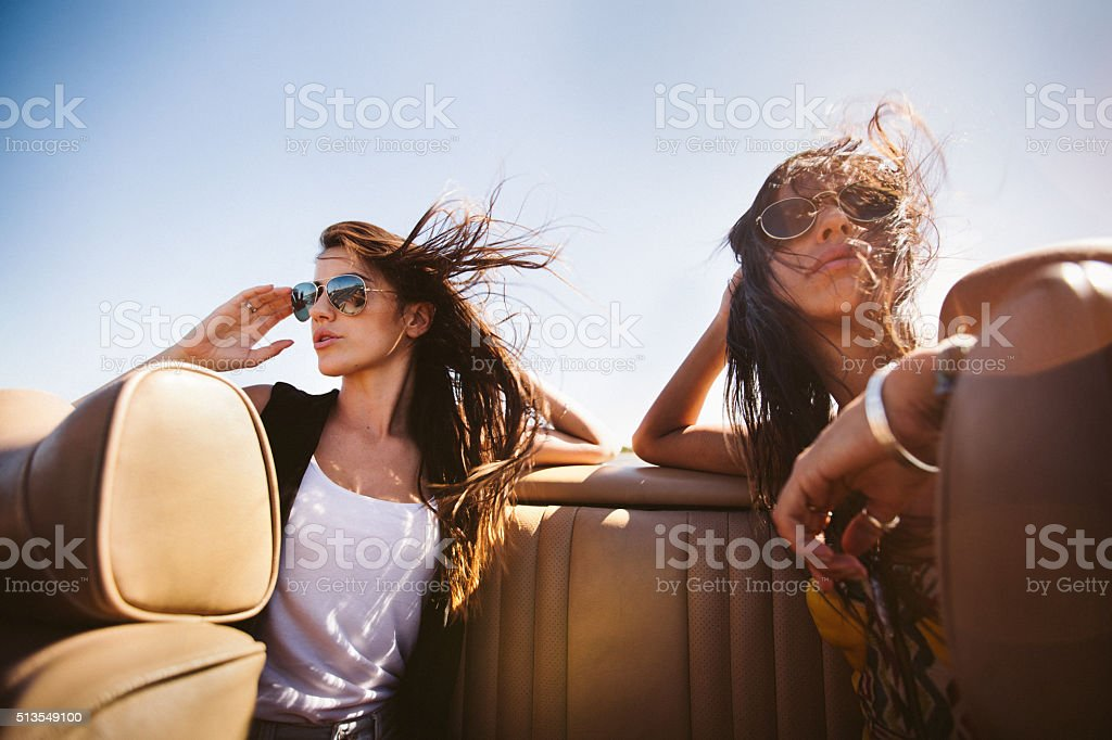 Two female friends relaxing and enjoying a road trip on the back seat...