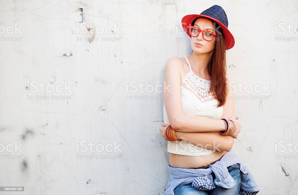 Hipster boho woman posing on a wall stock photo