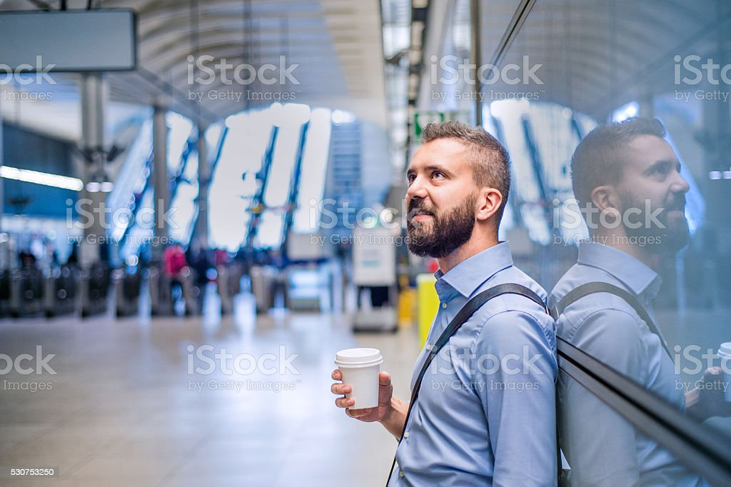 Hipster businessman holding a coffee cup, subway station stock photo