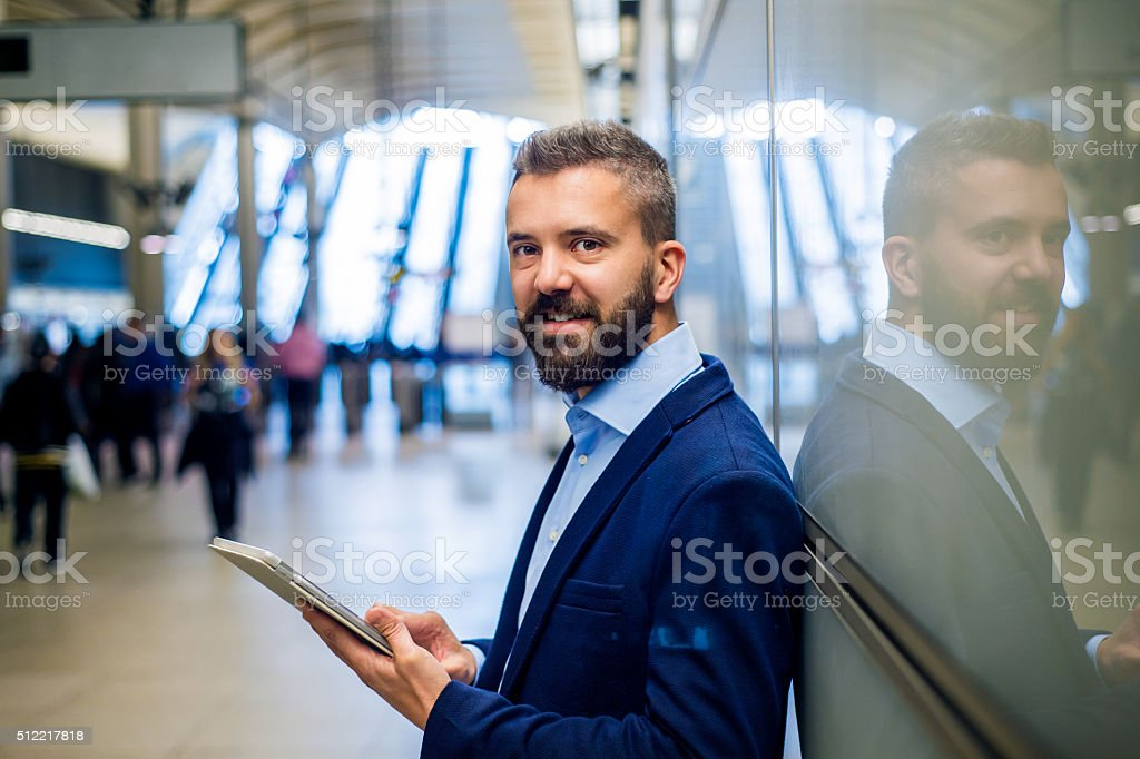 Hipster businessman holding a tablet, standing on subway station stock photo