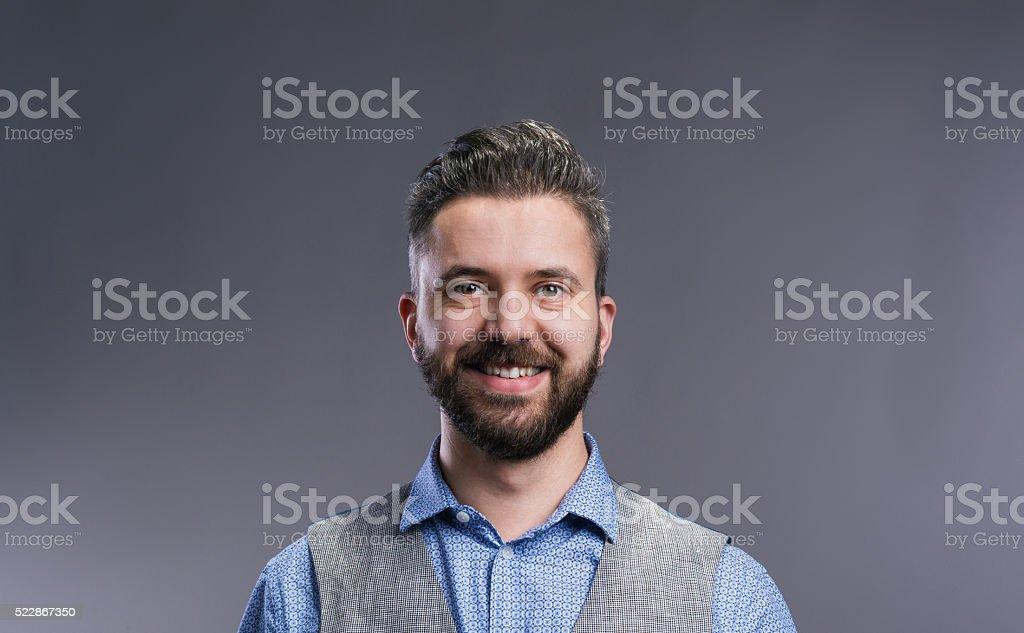 Hipster businessman in blue shirt, studio shot, gray background stock photo