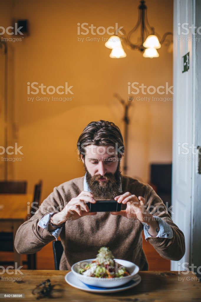 Hipster businessman taking a picture of his meal stock photo