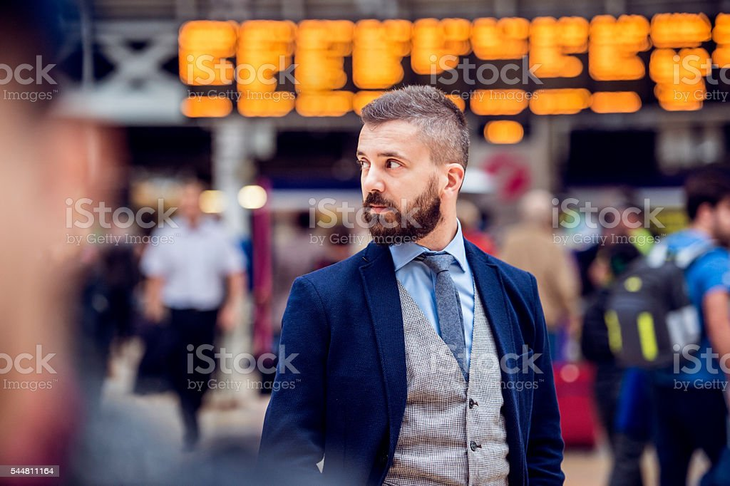 Hipster businessman waiting at the crowded London train station stock photo