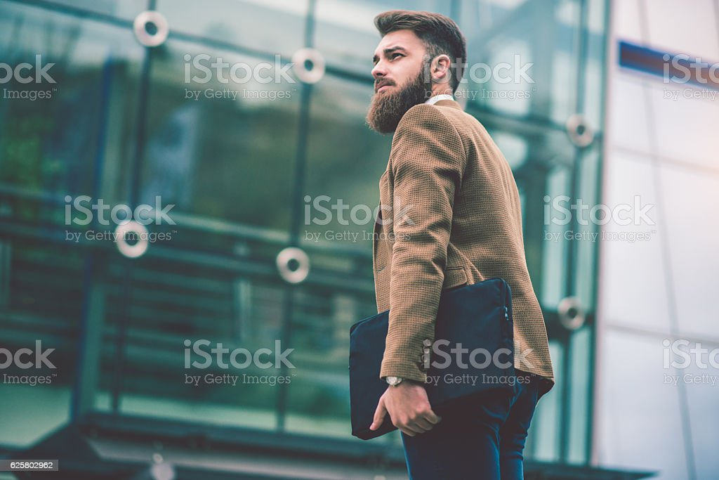 Hipster Businessman with Laptop Bag Walking on the City Street stock photo