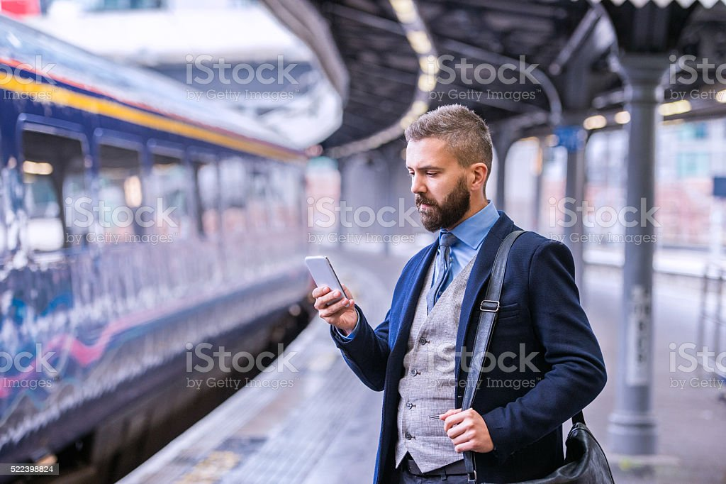 Hipster businessman with smartphone, waiting at the train platfo stock photo