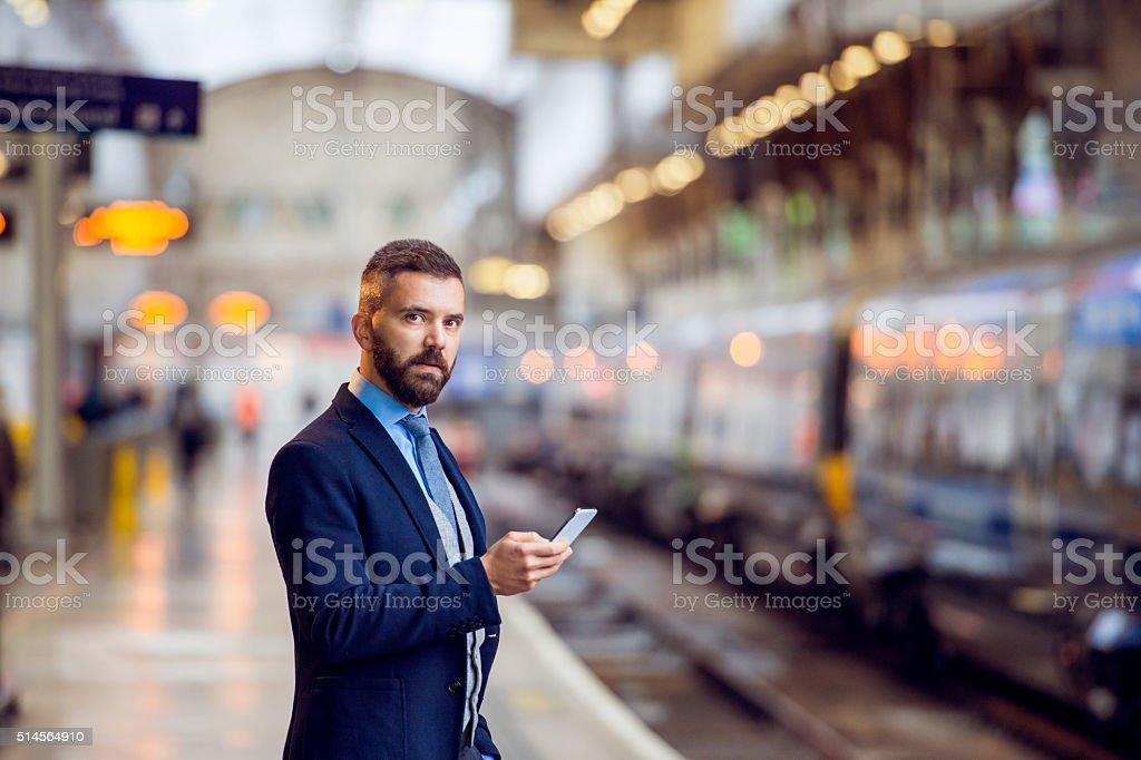 Hipster businessman with smartphone, waiting, train platform stock photo