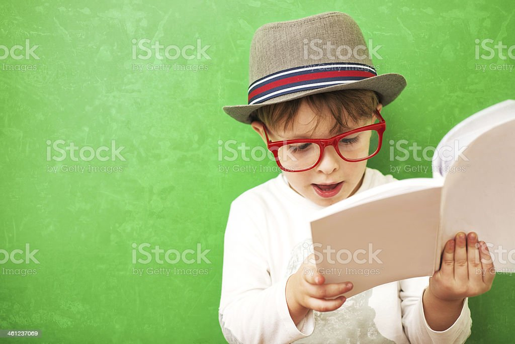 Hipster Child Reading a Book on Green Background stock photo