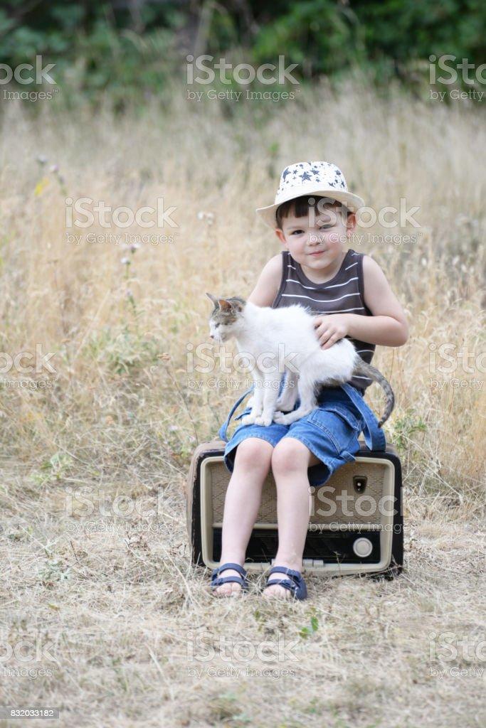 Little boy listens to music through an old radio