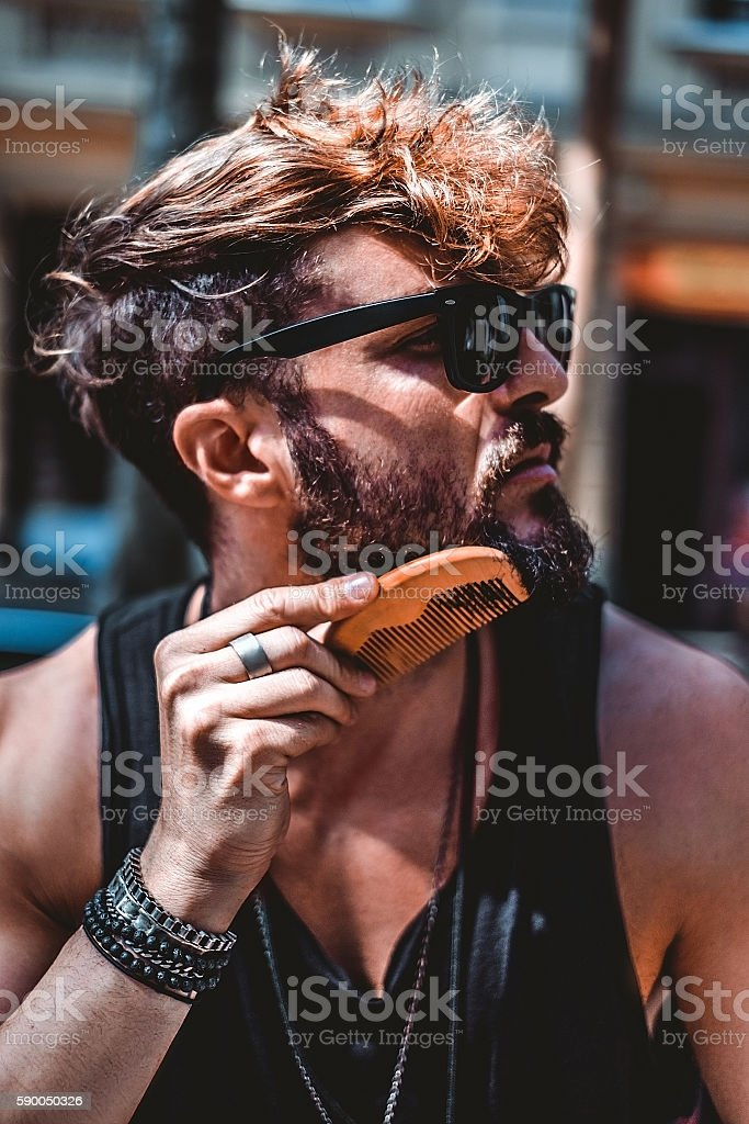 Hipster combing beard on a sunny day stock photo