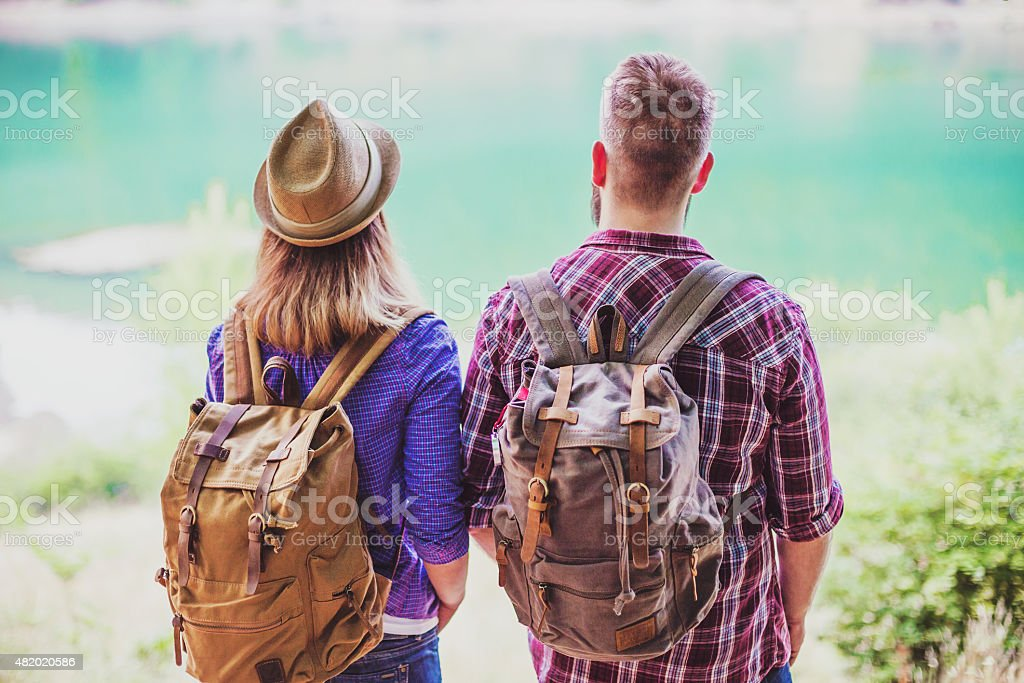 Hipster couple backpacking and enjoying view at the lake stock photo