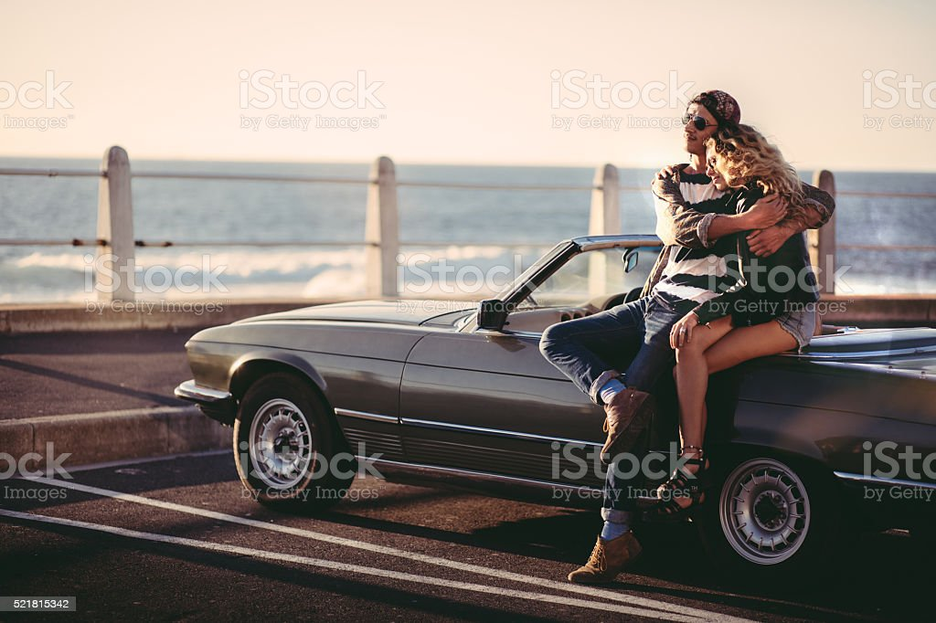 Hipster young couple enjoys a sunset embraced during a road trip with...