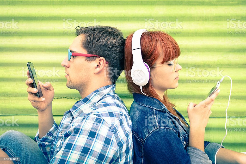 Hipster couple in disinterest moment with mobile smart phones stock photo