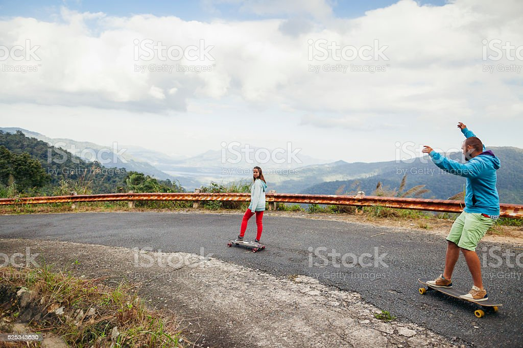 hipster couple longboarding extremely in tropcis stock photo