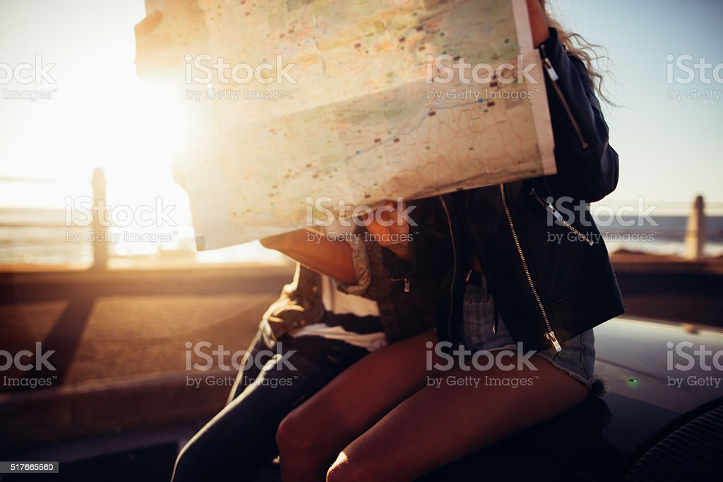 Hipster couple looking map on summer road trip with convertible stock photo