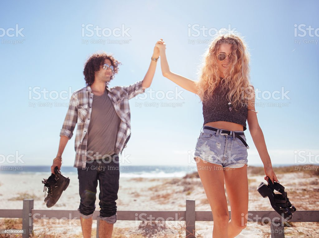 Hipster couple walking together barefoot towards van from beach stock photo