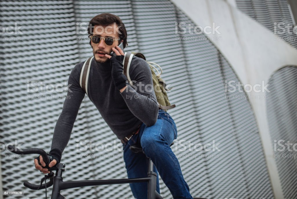 Hipster cyclist talking on the mobile phone stock photo