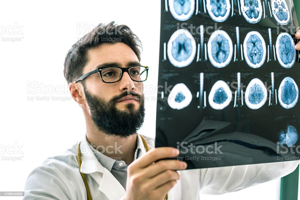 Hipster Doctor examining the x-ray of brain stock photo