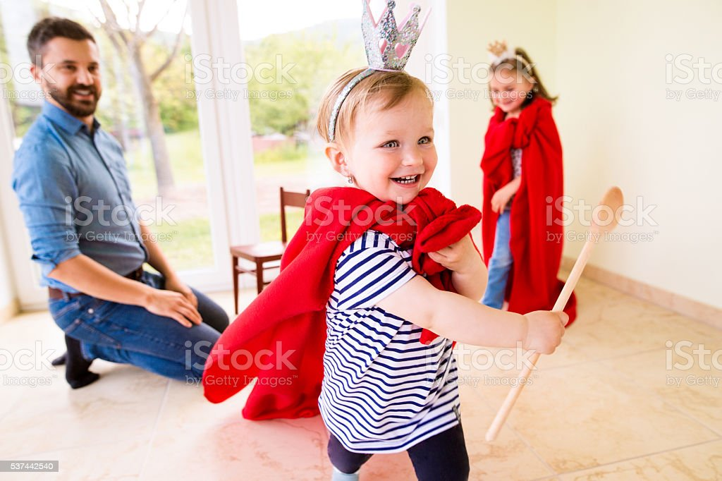 Hipster father with his princess daughters wearing red capes stock photo