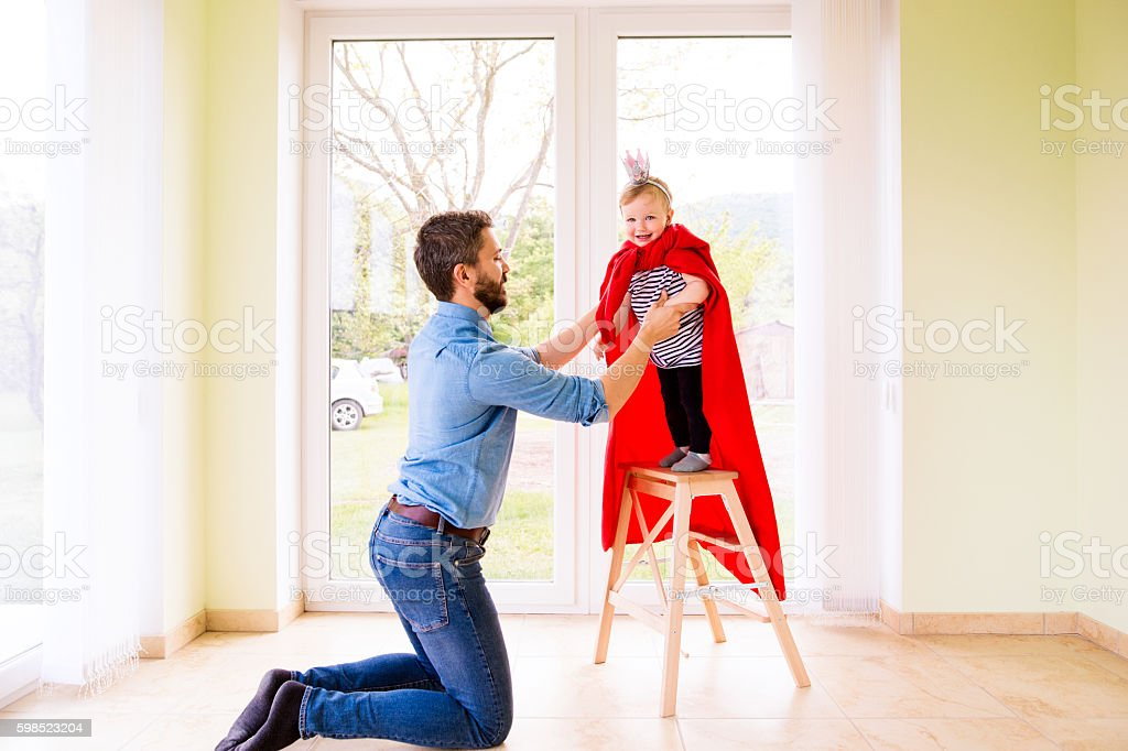 Hipster father with princess daughter jumping into his arms stock photo