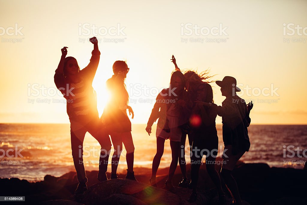 Hipster friends dancing in sunset light at a beach stock photo