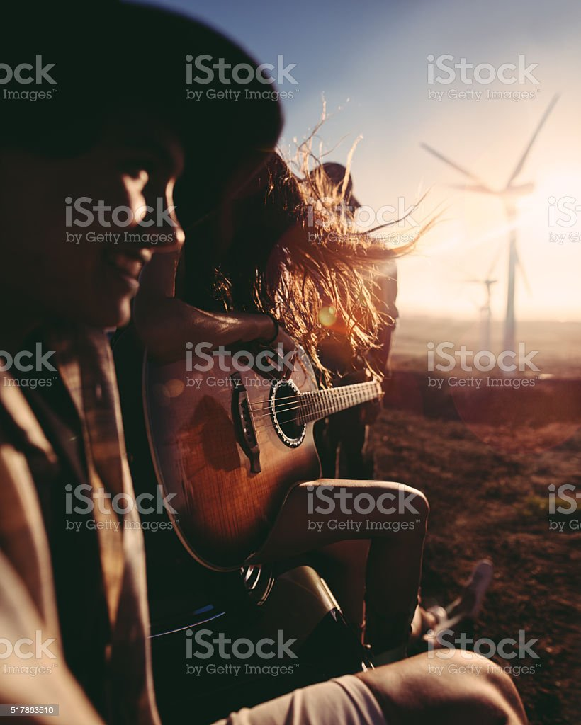 Hipster friends enjoying road trip with a guitar during sunset stock photo