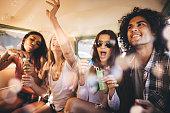 Hipster friends having bubbles party inside a vintage van