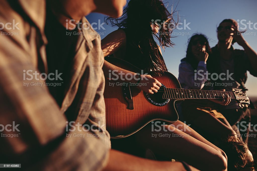 Hipster Friends having fun singing together with a guitar outdoors stock photo