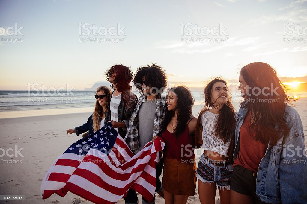 Hipster friends holding an American flag during a beach walk stock photo