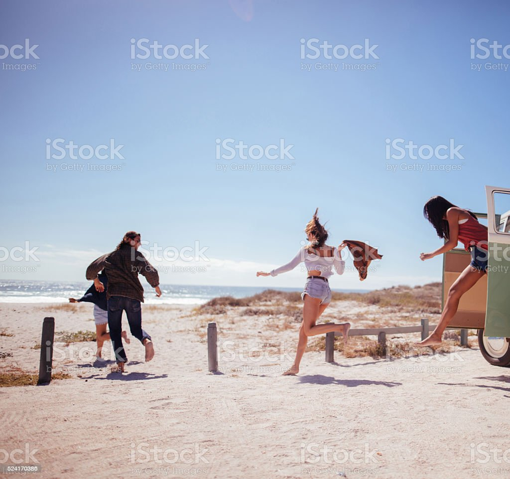 Hipster friends jumping out of Road Trip van at beach stock photo