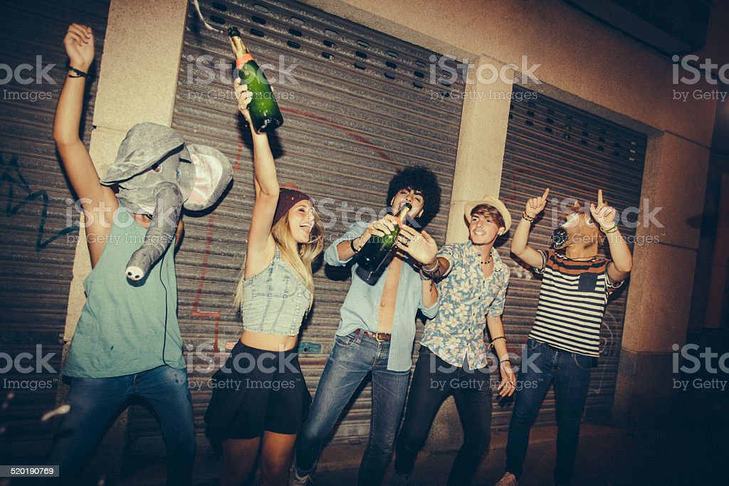 Hipster Friends Popping Champagne In Street stock photo