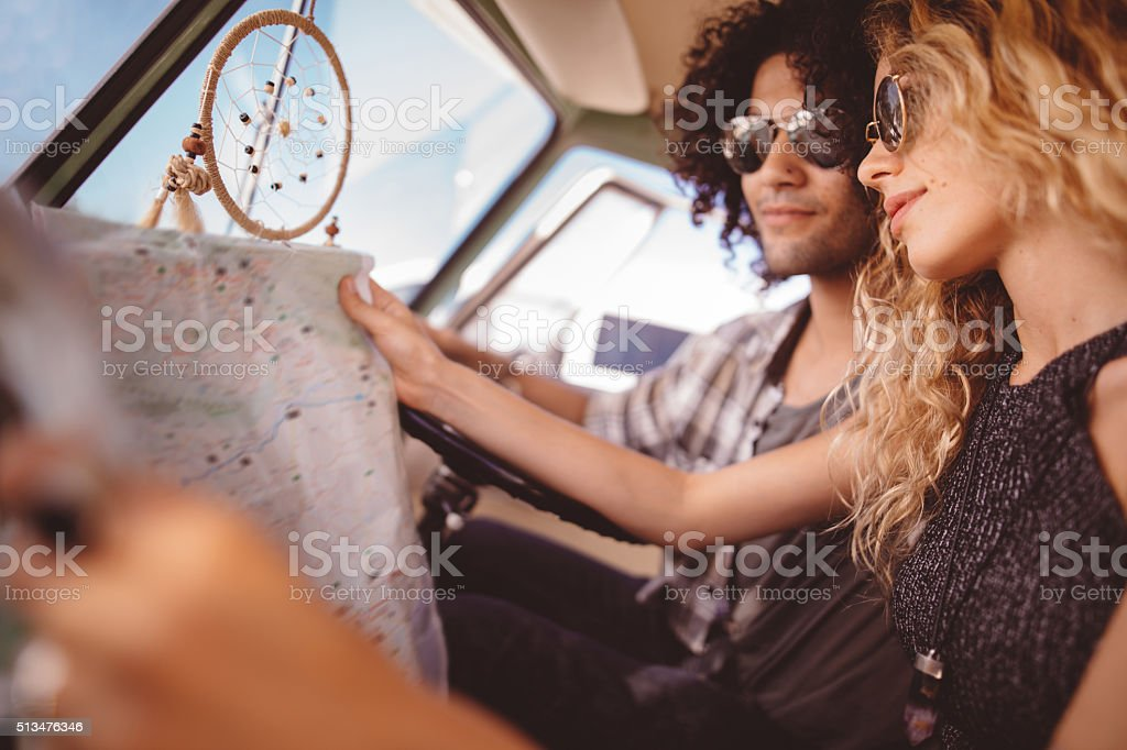Hipster Friends Sitting in Retro Van Looking at Map stock photo
