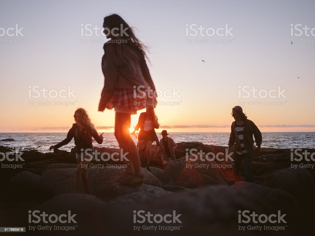 Hipster friends walking on rocks at beach on summertime sunset stock photo