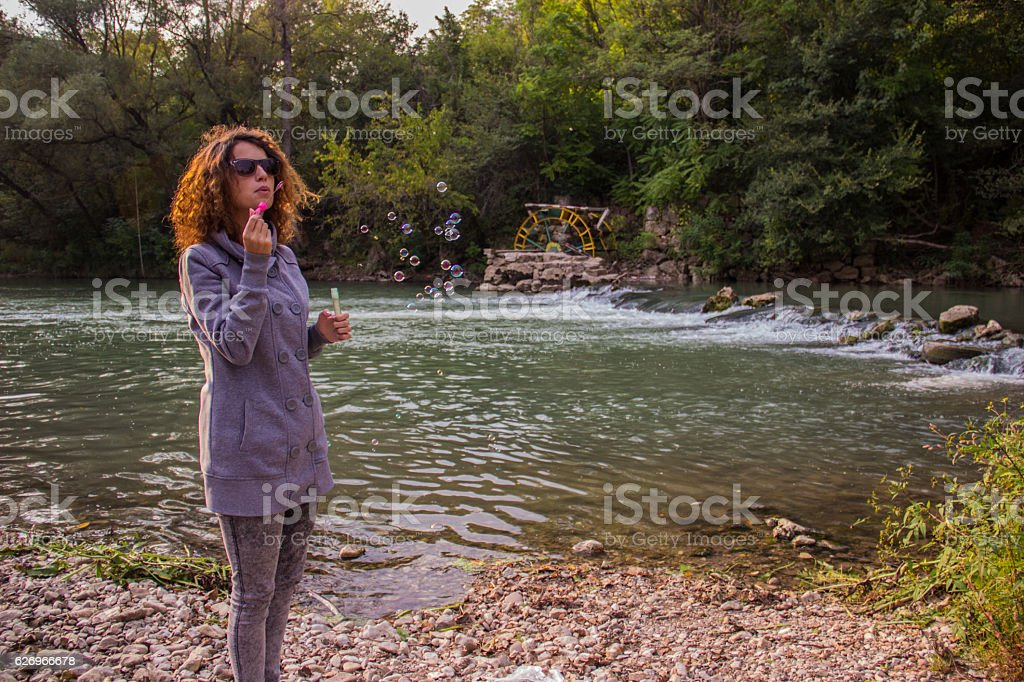 Hipster girl blowing bubbles in nature royalty-free stock photo