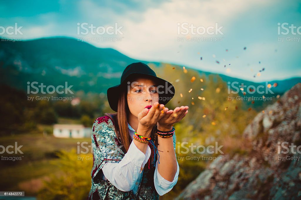 Hipster girl blowing confetti stock photo