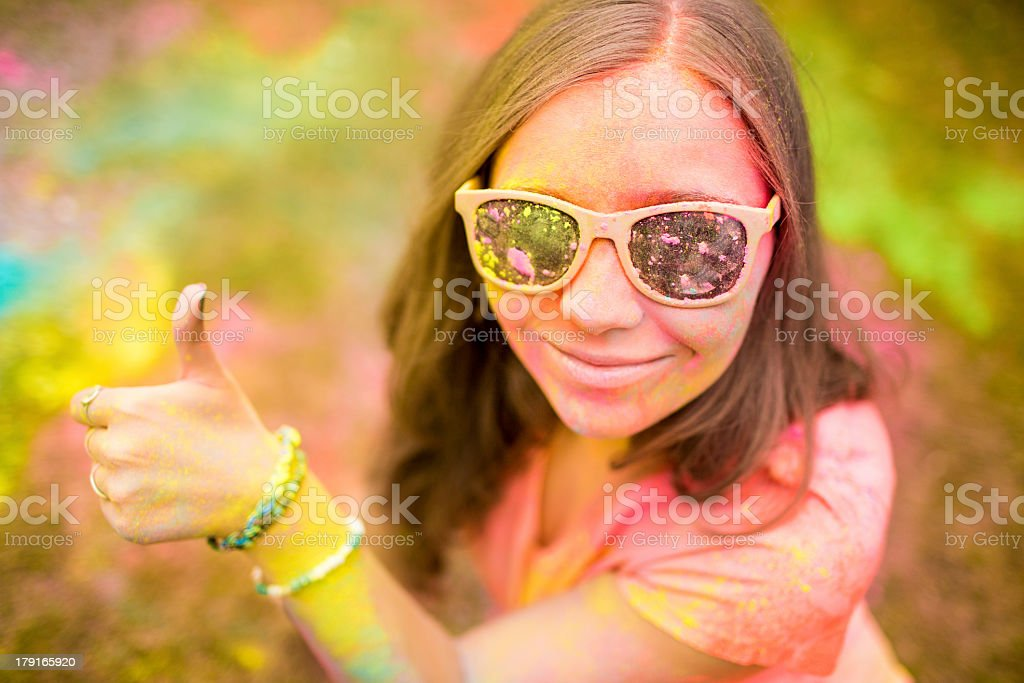 Hipster girl gibing thumbs up at colorful Holi Festival royalty-free stock photo