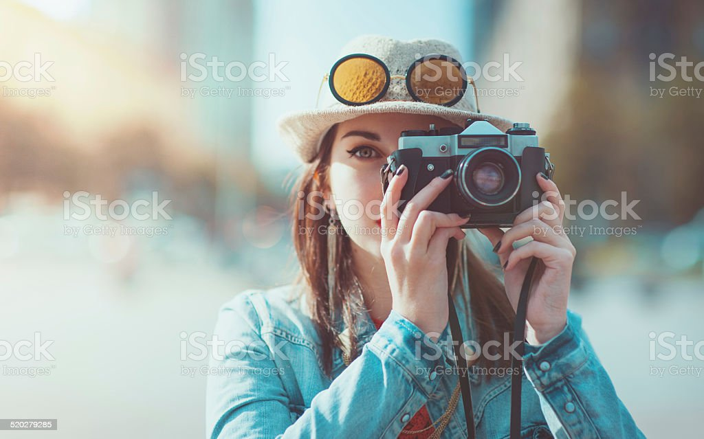 Hipster girl making picture with retro photocamera, focus on camera stock photo