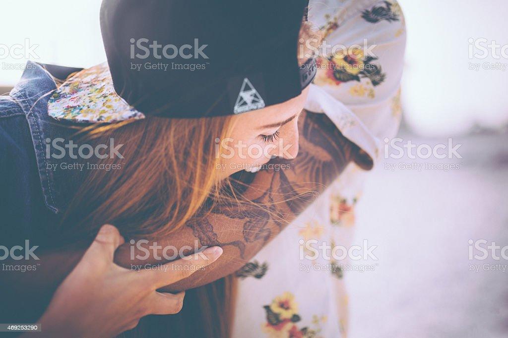 Hipster girl playfully pretending to bite her boyfriend's tattoo stock photo