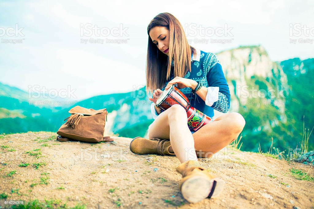 Hipster girl playing djembe stock photo