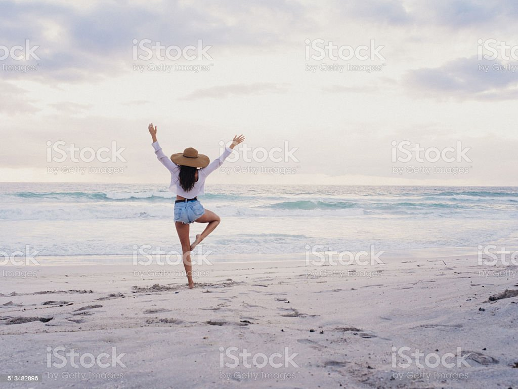 Hipster Girl Practicing Yoga Pose on Beach stock photo