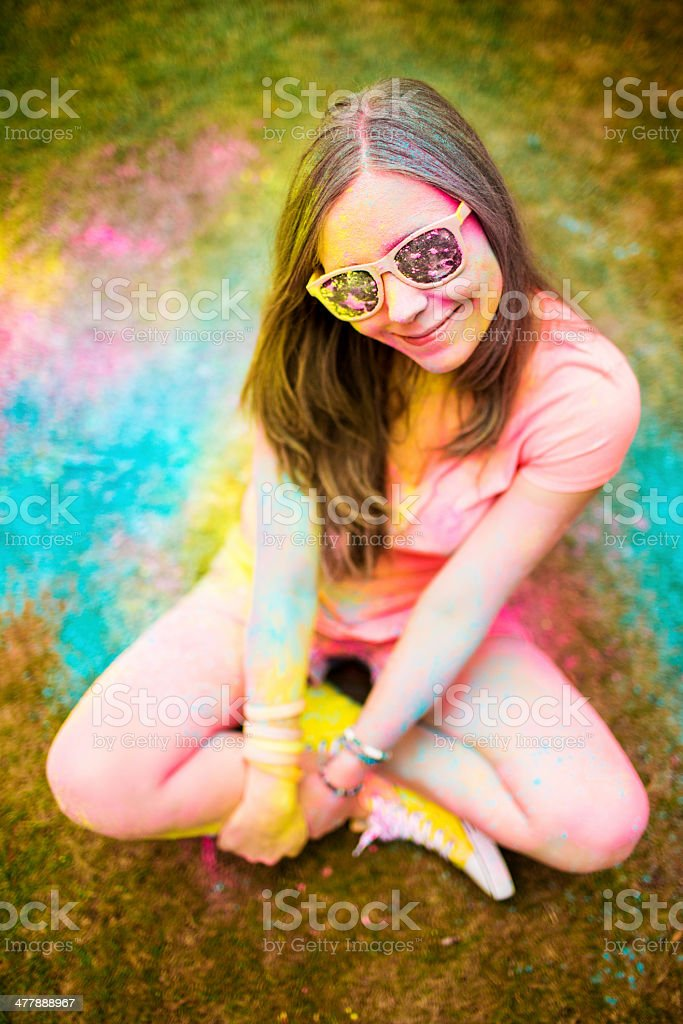 Hipster girl sitting at Holi Festival with colorful powder royalty-free stock photo