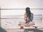Hipster girl sitting on her skateboard at the beachfront