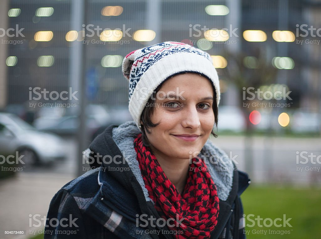 Hipster girl standing in front of the lights at dusk royalty-free stock photo