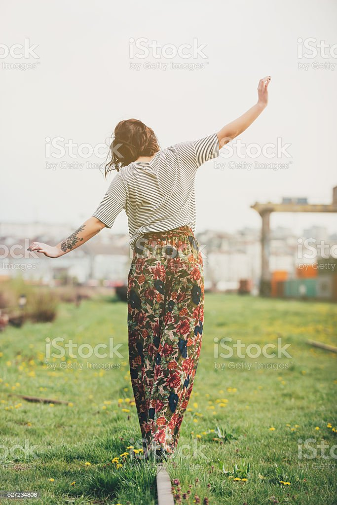 Hipster girl walking on railroad tracks stock photo