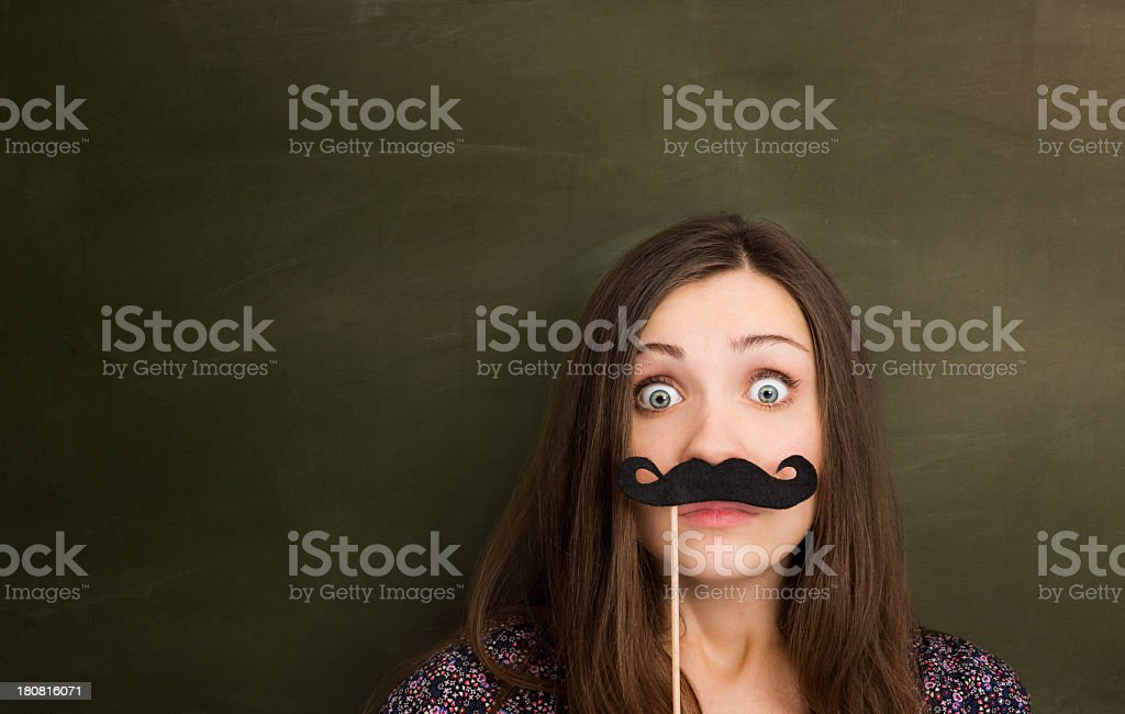 Hipster girl with mustache in front of empty blackboard. stock photo