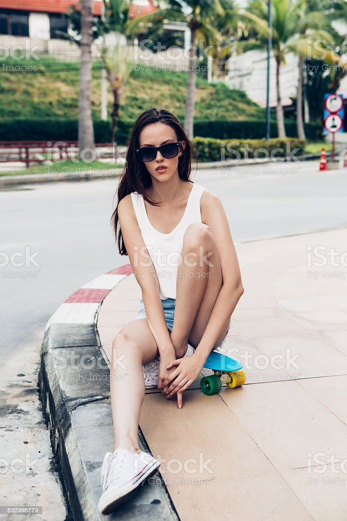 Hipster girl with skateboard on the street. stock photo