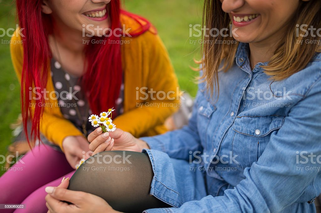 Hipster girls laughing and picking flowers stock photo