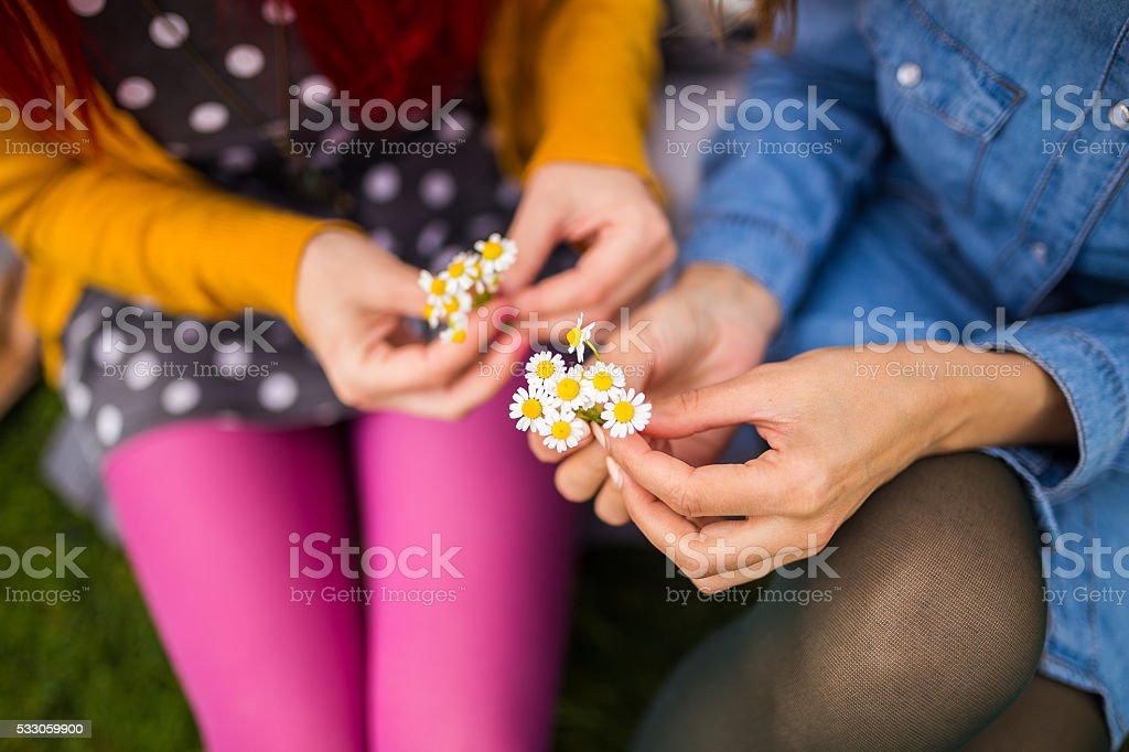 Hipster girls picking flowers stock photo